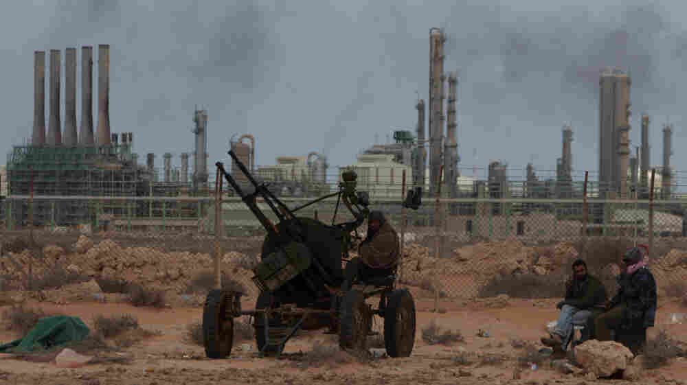 Rebels fighting forces loyal to Libyan leader Moammar Gadhafi take up position in front the oil refinery complex in Ras Lanouf, eastern Libya, March 10.