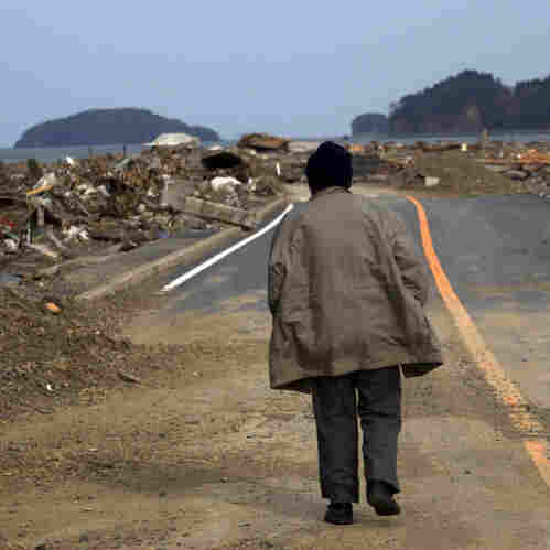 A Japanese earthquake and tsunami survivor walks alone Monday on a road past the destroyed village of Saito in northeastern Japan.