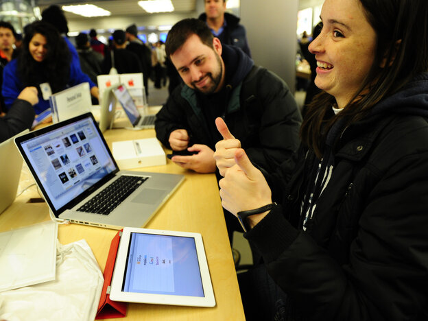A customer reacts after trying the iPad 2 at the Apple store on Fifth Avenue in New York on Friday.