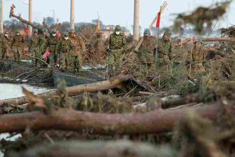 Members of the Japanese military walk through tsunami wreckage in Sendai, Japan on Sunday.