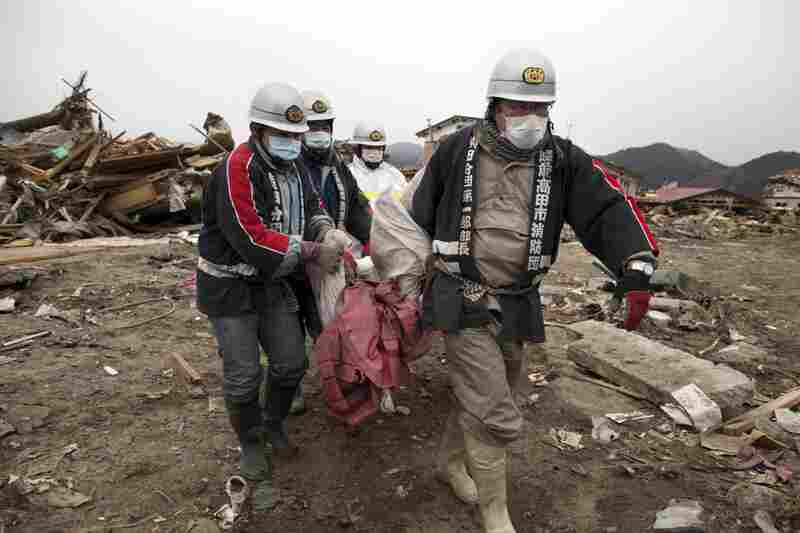Rescue workers carry a body from the rubble in Rikuzentakata, Iwata prefecture in northeastern Japan on Tuesday.