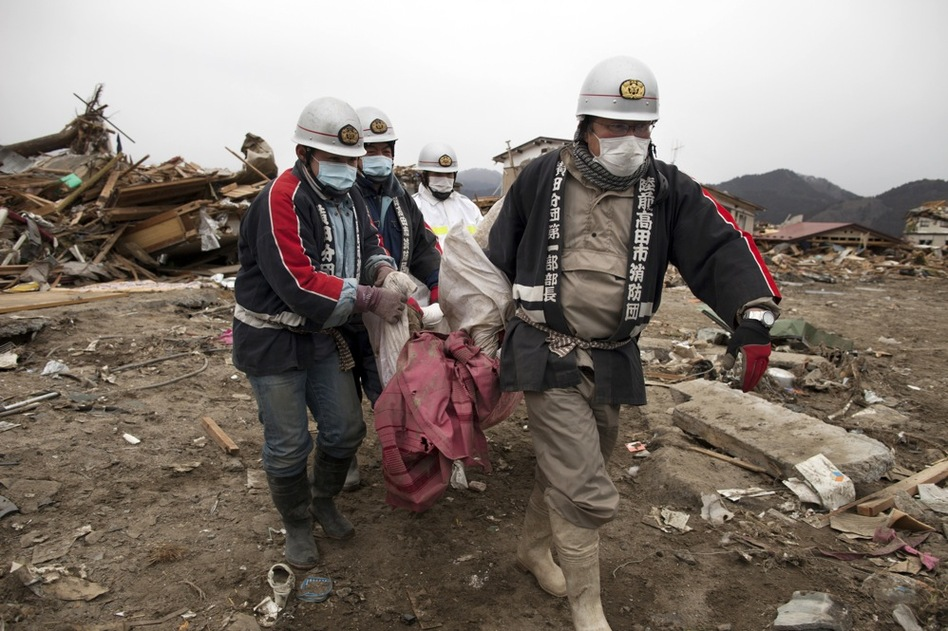 Rescue workers carry a body from the rubble in Rikuzentakata, Iwata prefecture in northeastern Japan on Tuesday.  (Getty Images)
