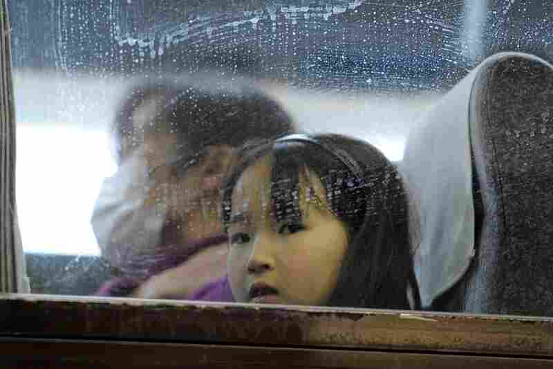 A young girl looks out from a bus window as people rush to get out of the city in Yamagata northern Japan on Tuesday.