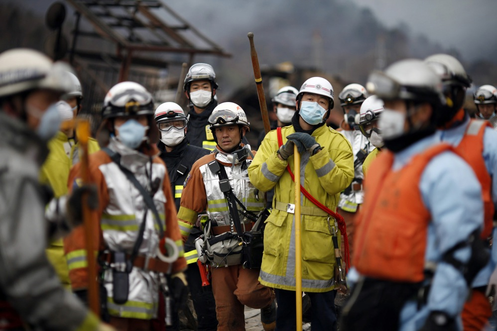 Civil defense teams search for survivors in Otsuchi, Japan on Tuesday.
