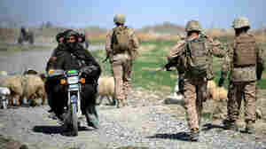 Three Afghan men on a motorcycle passed by as U.S. Marines patrolled last month in Afghanistan's Helmand Province.