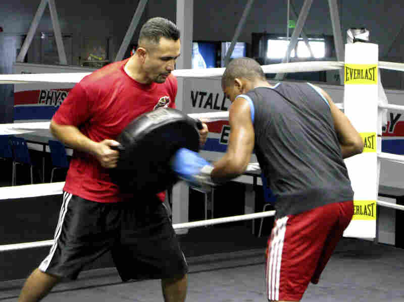 L.A. Matadors head coach Manny Robles works with a team member during training session at The Rock boxing gym in Carson, Calif.