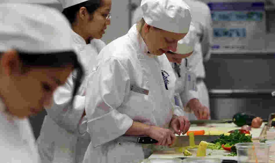 A culinary student cuts vegetables during a class at the Cordon Bleu program at the California Culinary Academy in San Francisco in 2009. Students are pouring into culinary schools to pursue their dreams. But once they graduate, many of them face a mountain of debt — and low starting salaries.