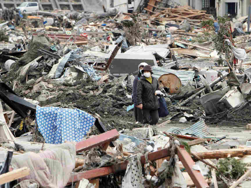 People walked through rubble in Minami-Sanrikucho, Miyagi prefecture, earlier today (March 15, 2011).