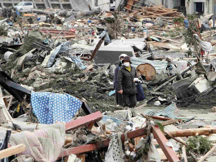 People walked through rubble in Minami-Sanrikucho, Miyagi prefecture, earlier today (March 15, 2011).