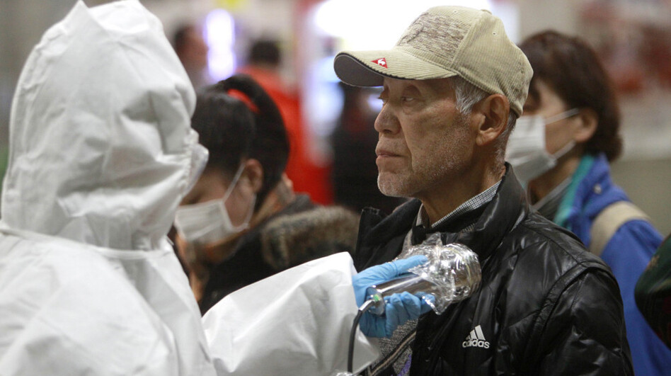 An evacuee is screened for radiation exposure at a testing center on Tuesday in Koriyama city, Fukushima prefecture. Officials are concerned about radiation leaking from the nuclear plant nearby.