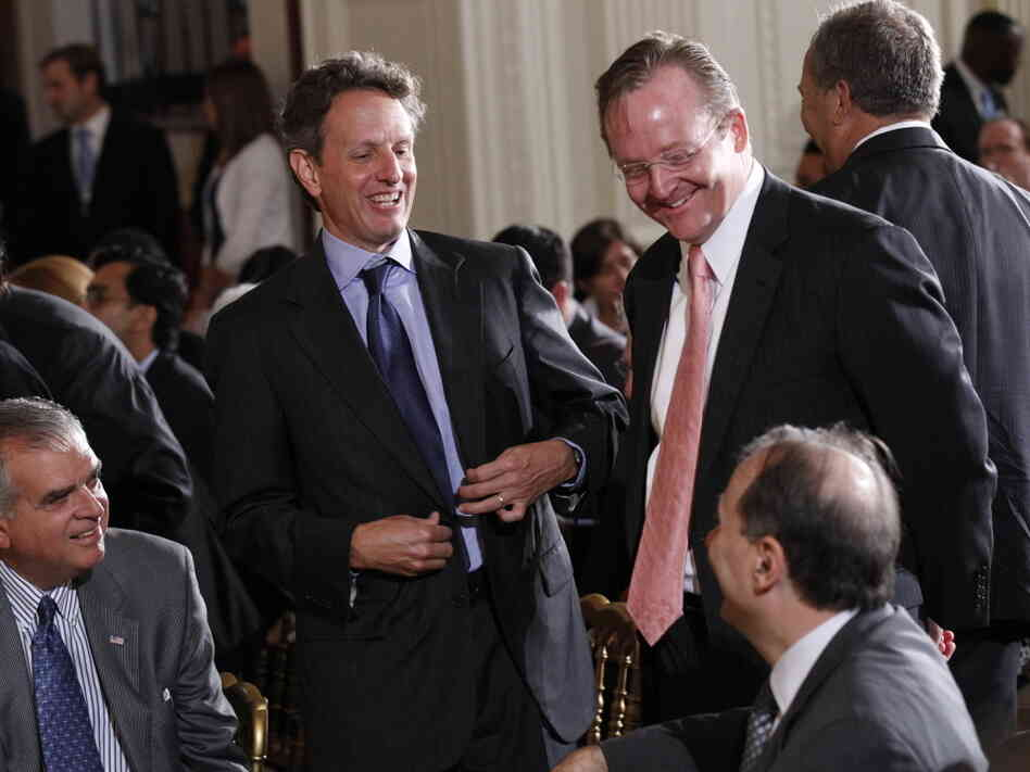 Treasury Secretary Timothy Geithner, standing left, shares a laugh with David Axelrod, seated right, October 2010.