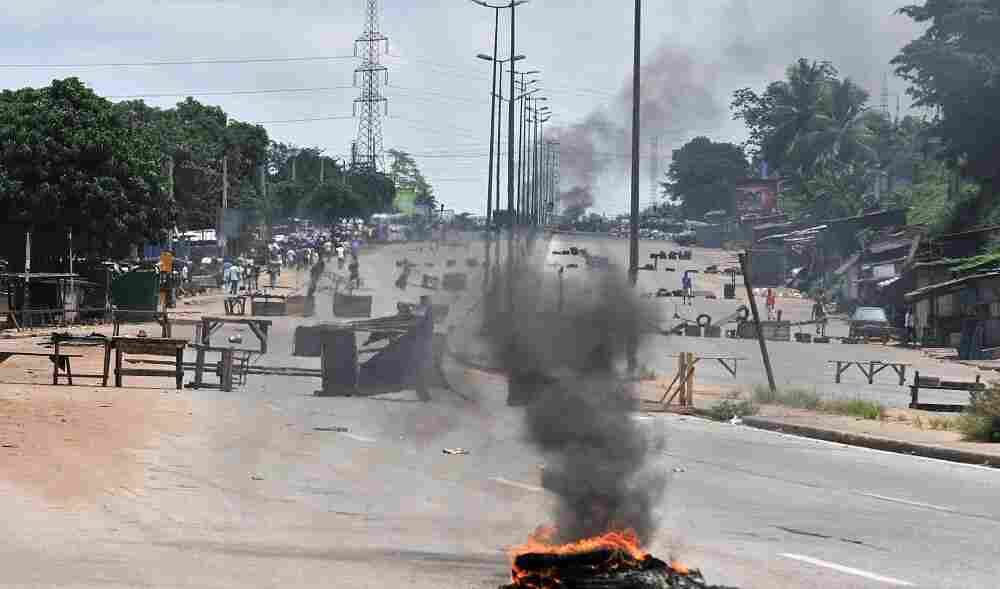Residents walk past barricades and burning tires on the main road leading to the Abobo district of Abidjan.