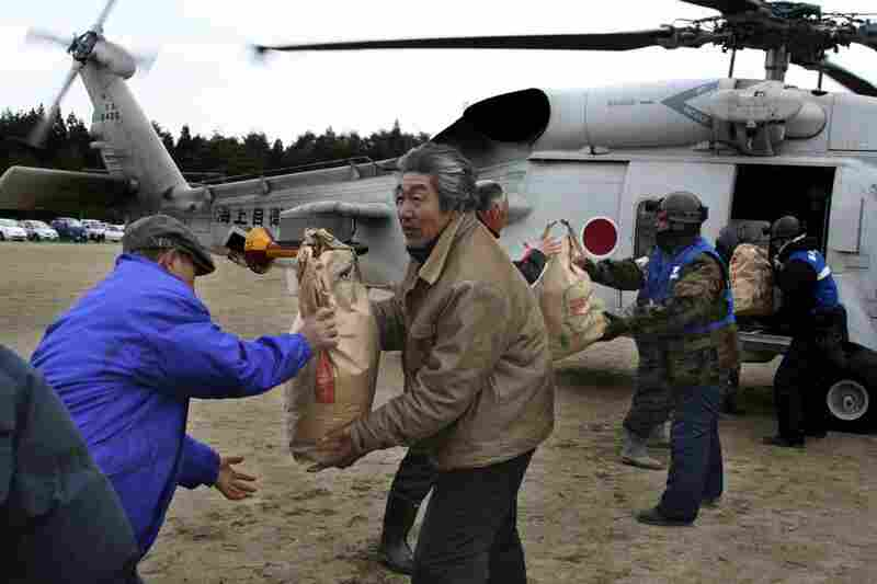 Rescuers and victims carry out bags of food aid from a helicopter in Yamada, northern Japan.
