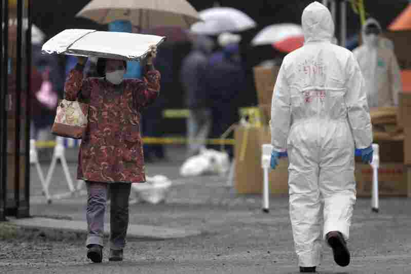 A woman carrying a heat blanket leaves a radiation emergency scanning center in Koriyama in Japan.