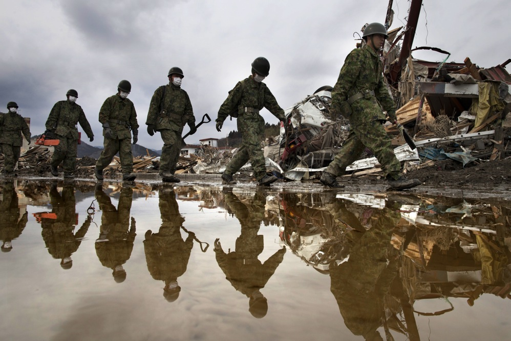 Japanese military march during a search and rescue mission scouring the rubble of a village in Rikuzentakata, Miyagi prefecture, Japan.