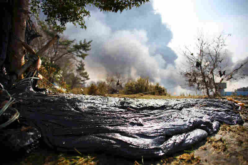 Tar from a burning oil refinery lies on a river bed near Sendai, northern Japan.