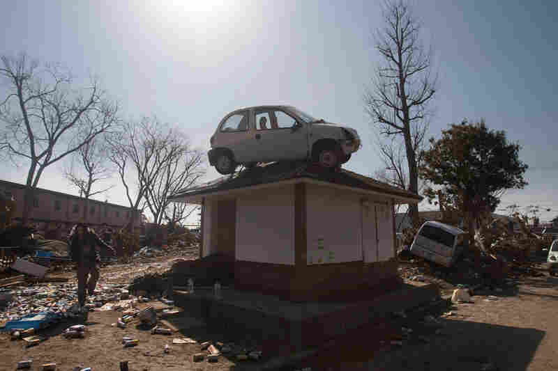 A car, washed into the area by the tsunami, sits on top of a small building in a destroyed neighborhood in Sendai, Japan.