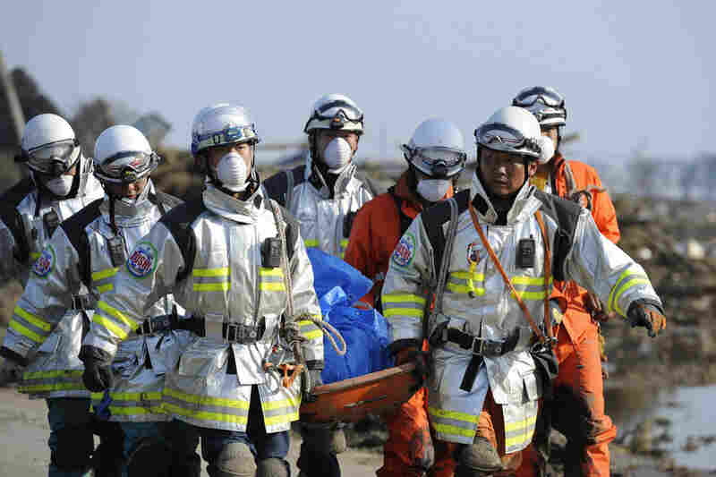 Japanese rescuers carry a body in Sendai.