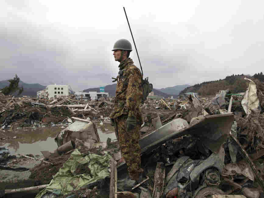A Japanese soldier stood watch earlier today (March 15, 2011) over the rubble of what was Rikuzen-Takada City in Japan.