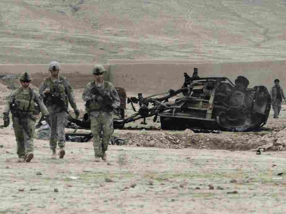 U.S. soldiers pass car wreckage after an explosion in Kandahar province, Afghanistan, February 2011.