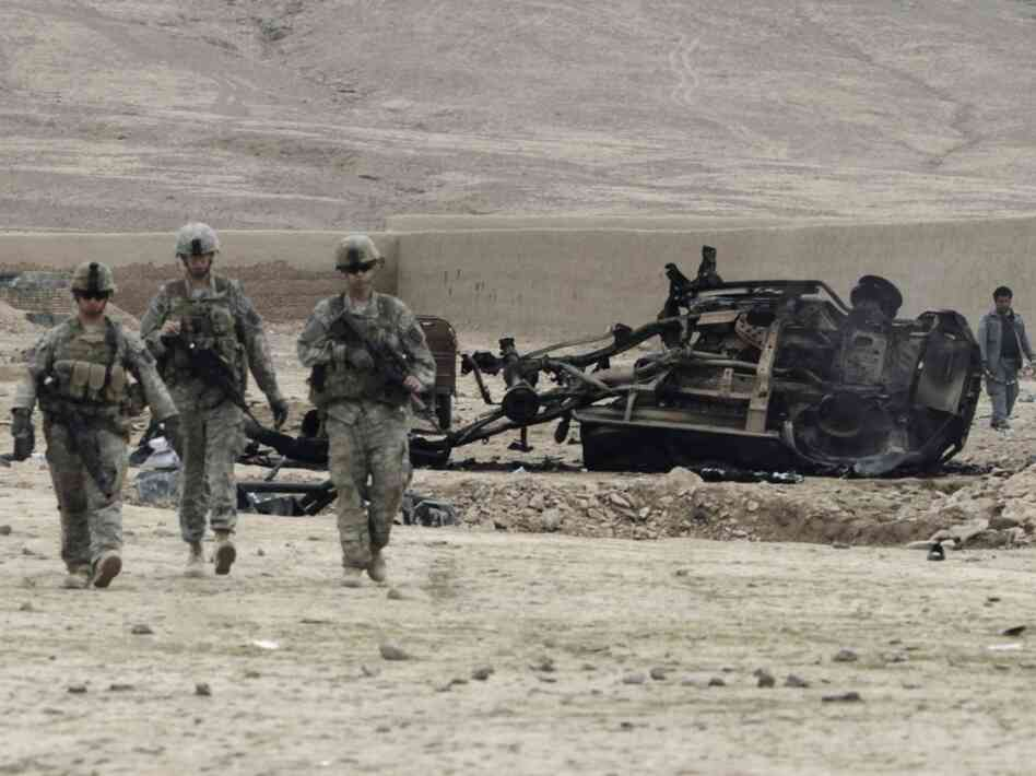 U.S. soldiers pass car wreckage after an explosion in Kandahar province