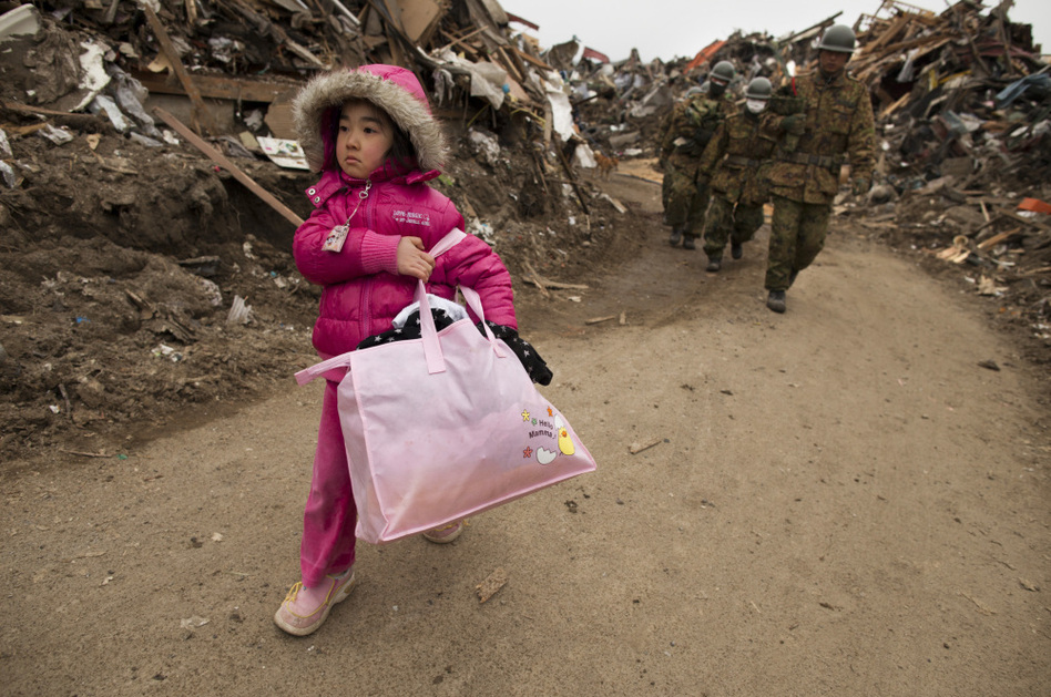 Riku Zentaka, Japan: Neena Sasaki, 5, carries some of the family belongings from her home that was destroyed after the devastating earthquake and tsunami. (Paula Bronstein/Getty Images)