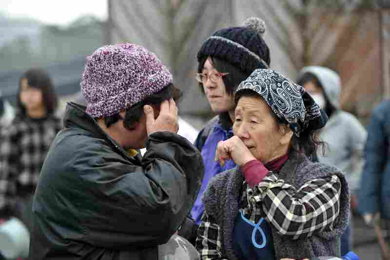 Two women wait for water at a distribution point in Ofunato northeastern Japan.