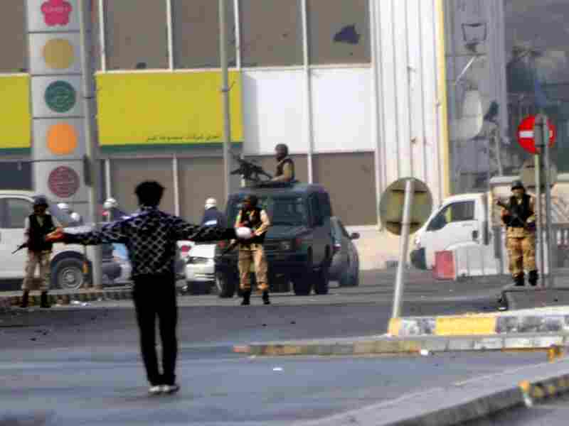A protester stands open-armed in front of the military in Pearl Square in the Bahraini capital of Manama on Wednesday, after Bahraini police stormed a protest camp, an opposition party official said.
