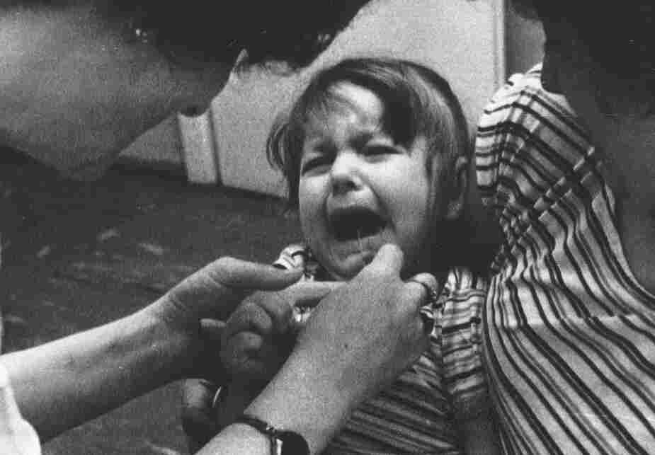A nurse at a children's health clinic in Warsaw administers an iodine solution to a 3-year-old girl held in her mother's arms in Poland, May 1986, as a protective measure against possible radiation poisoning after the Chernobyl disaster.