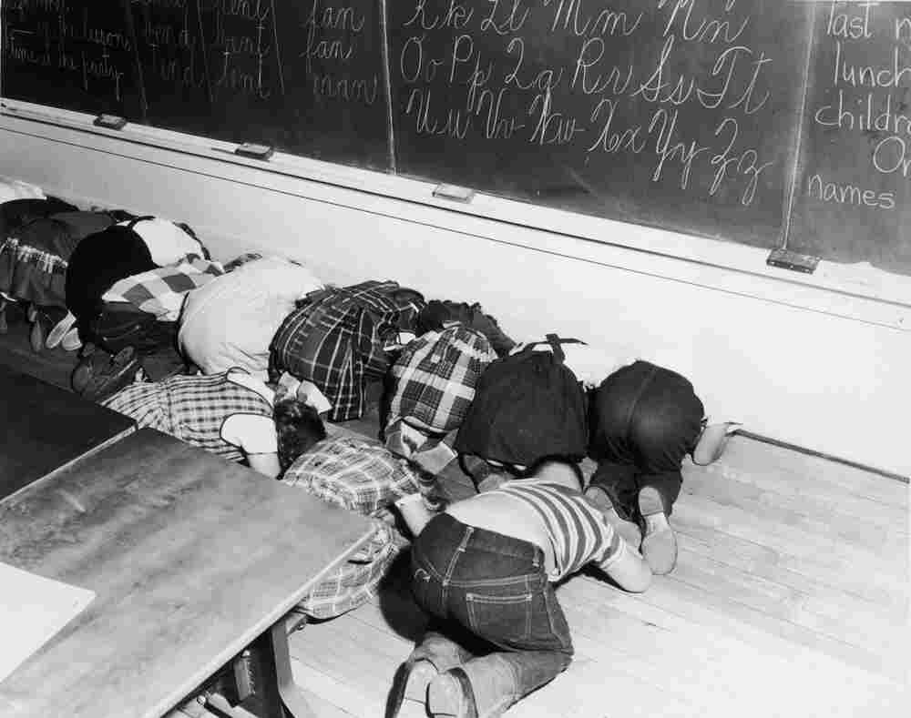 "Schoolchildren kneel to practice a ""duck and cover""  air-raid drill in an elementary school classroom, circa 1955."