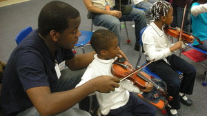 Stanford Thompson, another Abreu Fellow alum, adjusts a student's bowing in a nucleo in Philadelphia.