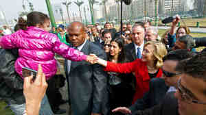 Secretary of State Hillary Clinton (in red) shook hands with a child as she visited Cairo's Tahrir Square earlier today (March 16, 2011).