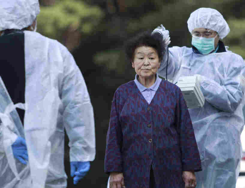 Officials check the level of radiation on a woman in Fukushima pre