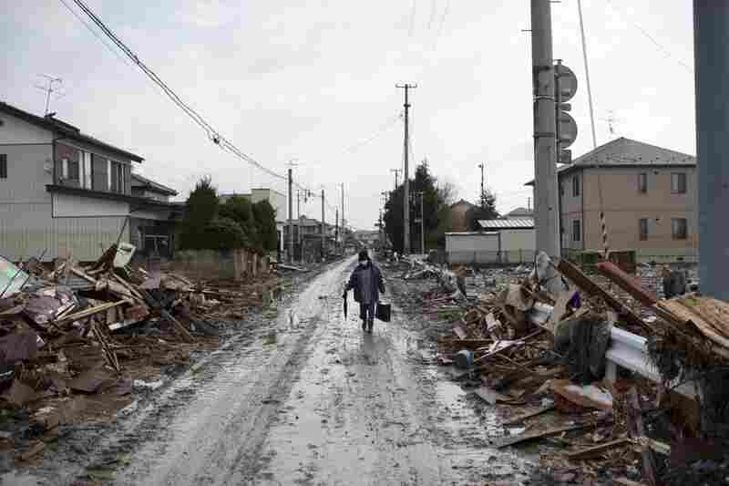 A resident walks along a road lined with debris in Sendai, Miyagi prefecture on Wednesday.