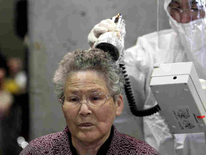 A woman is scanned for radiation exposure at a temporary scanning center for residents near the Fukushima Dai-ichi nuclear power plant in Koriyama, Fukushima prefecture.