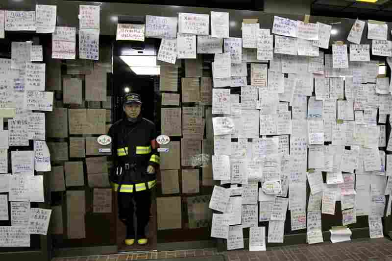Survivors' notes seeking information about missing relatives and friends hang on the entrance of Natori City Hall in Natori, Miyagi prefecture.