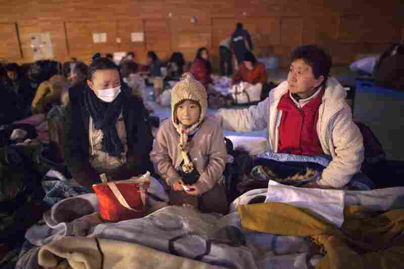 Yukie Ito, (L) tries to comfort her daughter Hana,8, (C) with grandmother Tamiyo (R) at a cold refugee center for the homeless  in Kesennuma, Miyagi province.