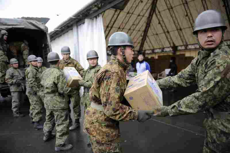 Members of the Japanese military load relief goods at the port in Kamaishi City, Iwate prefecture.