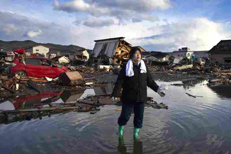 Chieko Chiba walks through the rubble after visiting her destroyed home in Kesennuma, Miyagi province.