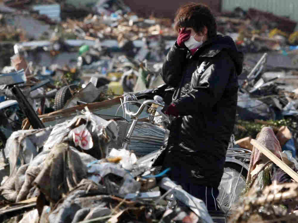 A woman reacts in the debris after her house was totally destroyed by the recent tsunami at Sendai in Miyagi prefecture on March 16, 2011.