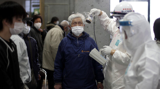 A man is scanned for radiation exposure at a temporary center for residents living close to the damaged Fukushima Daiichi plant on Wednesday, March 16, 2011.