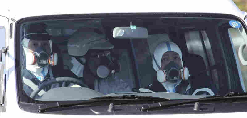 Police officers wear gas masks while on patrol in a vehicle at the Fukushima nuclear power plant on March 12. Experts are concerned about the safety of the nuclear workers, but they say that so far, there's no risk for others in Japan or in the U.S.