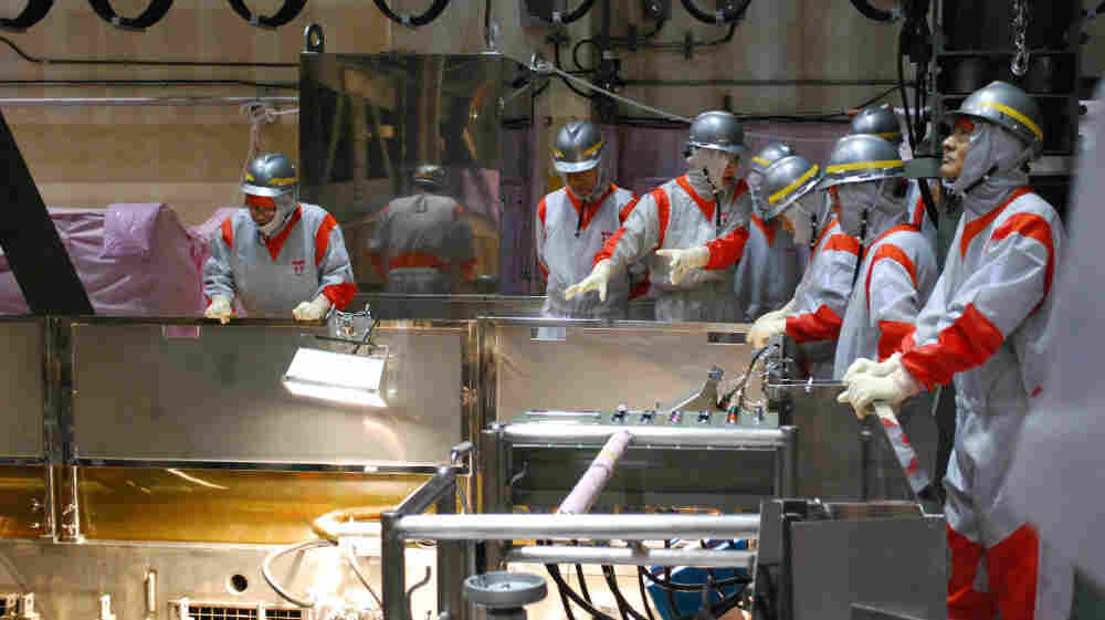 Government officials watch operations at a fuel storage pool inside the Fukushima No.1 plant's third reactor building last August, long before the earthquake that crippled the facility.