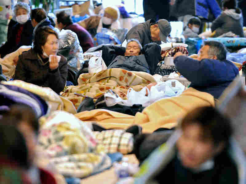 People rest on the floor at a evacuation center after the recent tsunami and earthquake in Natori, Miyagi prefecture, on Wednesday.