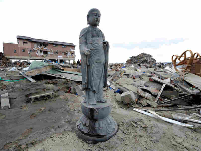 A religious statue stands amid the debris left by last Friday's tsunami in Natori, Miyagi prefecture. Many Japanese will turn to Shinto and Buddhist rituals as they cope with the disaster stemming from a powerful earthquake.