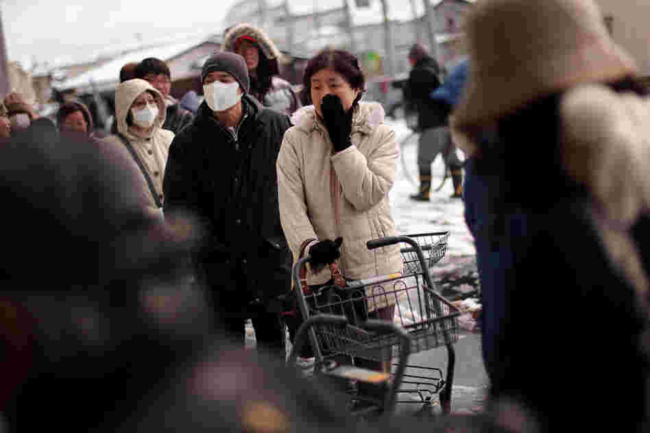 A woman waits in a line outside a grocery store in Ichinoseki.