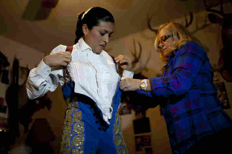 Raquel Martinez (right) the first female matador, helps Lopez prepare for a bullfight at the Santa Maria Bull Ring in La Gloria, Texas, on Jan. 23. Martinez is a friend of the Renks and a supporter of Lopez.