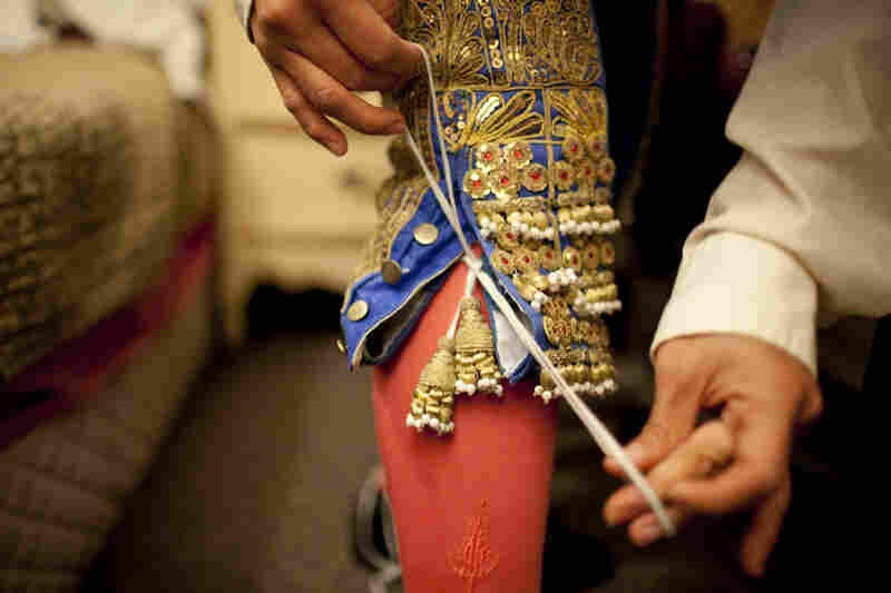 Lopez puts the finishing touches on her traje de luces, the uniform specially designed for bullfighters.