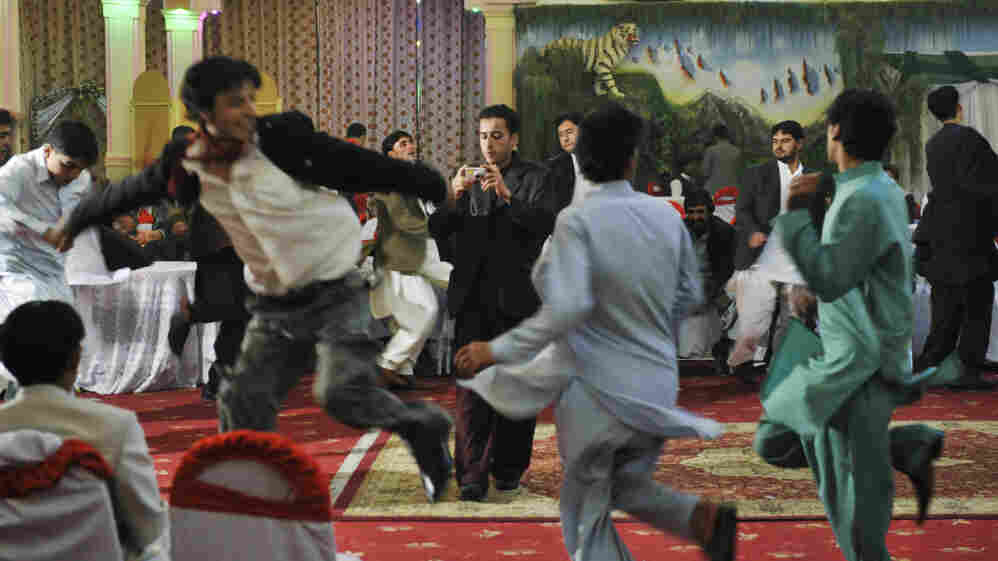 Afghan men dance at a wedding party in Kabul in October 2009. Celebrating weddings with dance and music returned to Afghanistan after the practice was banned during the Taliban regime. In a country where most Afghans are poor, this 600-guest reception cost about $5,000.