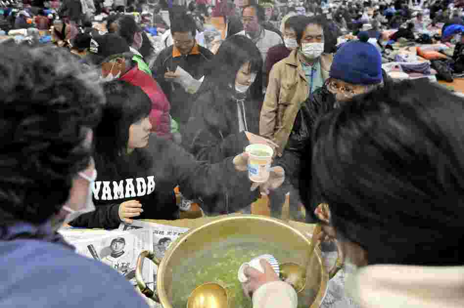Evacuees receive bowls of soup at a makeshift shelter in Yamada, northern Japan. Basic supplies remain scarce in regions heavily damaged by the earthquake and tsunami.